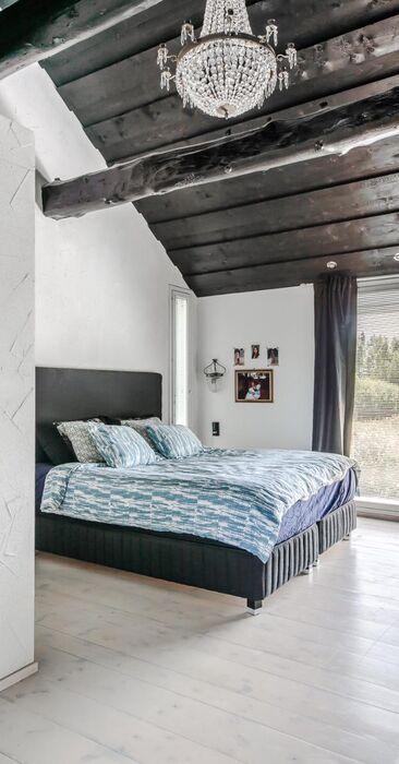 Näyttävä hirsikatto korkeassa makuuhuoneessa