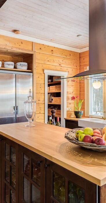Maalaiskartanon kaunis keittiö hirsiseinineen