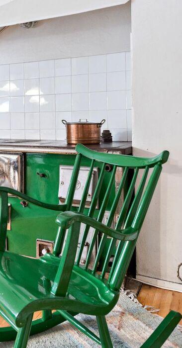 Vihreä keinutuoli ja puuliesi tuovat väriä keittiöön