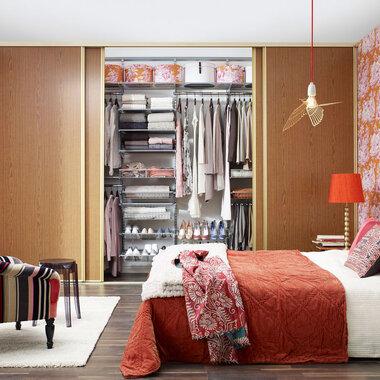 Makuuhuoneen lämminsävyinen sisustus reilun kokoisella säilytystilalla