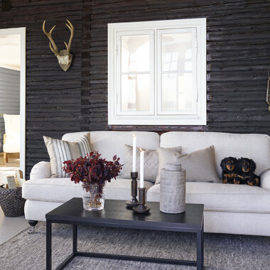 Klassinen, vaalea sohva erottuu tummaa seinää vasten