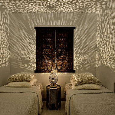 Kaunis valaisin luo hurmaavan kuvion koko huoneeseen